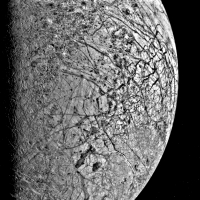Close-up of Europa from 241,000 kilometres (150,600 miles away). This Jovian moon has an unusually smooth (though cracked like an eggshell) surface, which implies that it may be mostly covered in ice. Suggestions of a sub-surface ocean of liquid water haved fuelled speculation about life having evolved there.