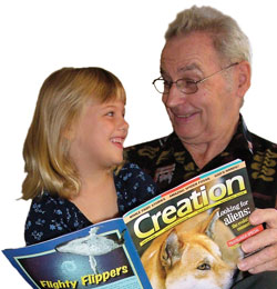 Man and girl reading Creation magazine