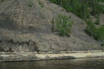 The embankment of Athabasca River near Fort McMurray reveals the dark grey oil sands of the McMurray Formation (classified as Lower Cretaceous) sitting on the white limestone of the Waterways Formation (classified as Middle Devonian). This implies a massive time gap yet the strata in the formations are parallel