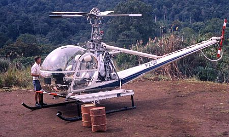 Des confers with helicopter pilot at crude helipad in his remote village in 1975.