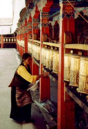 Buddhists don't pray to God, but believe they can earn merit by turning a prayer wheel as this woman is doing, while reciting the mantra written on it.