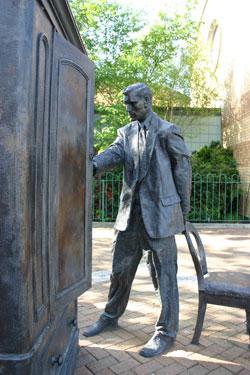 Фото 2. Статуя К.С. Льюиса, заглядывающего в платяной шкаф. Сцена из сказочного романа для детей «Лев, колдунья и платяной шкаф» 1950 года, события в котором разворачиваются в 40-х годах. Это произведение—самое известное из цикла «Хроники Нарнии», и было опубликовано первым из этой серии. Клайв Стейплз Льюис родился в Восточном Белфасте. В память о своем самом знаменитом романисте его жители установили эту статую недалеко от библиотеки Holywood Arches Library. Фото genvessel www.flickr.com.