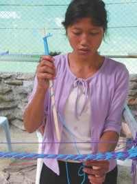 A Mlabri girl weaving